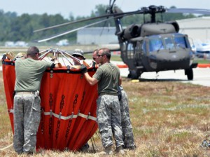 Florida National Guard aviation crewmembers prepare a water bucket to hook to a Black Hawk helicopter.