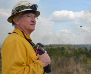 Paul Catlett provides oversight as Florida National Guard helicopters perform water-bucket operations for controlled burns used for training at Camp Blanding, April 2014.