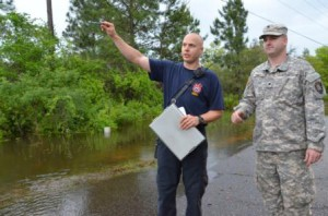 A member of the South Walton Fire Rescue points out flooded areas along a road near Santa Rosa Beach, Fla., to a Soldier from the Florida National Guard's 144th Transportation Company, April 30, 2014. More than 50 Florida Army National Guard Soldiers responded with high-water military vehicles to assist civilian first responders during flooding in Florida's panhandle. (Photo by Master Sgt. Thomas Kielbasa)