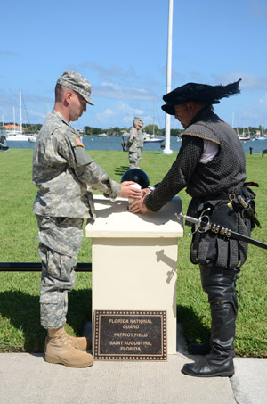 "The Florida Army National Guard's Staff Sgt. Jared Papesh and a re-enactor from Florida Living History place a cannister of soil representing a historic battlefield along the side of the newly dedicated ""Patriot Field"" during the 449th First Muster ceremony at the St. Francis Barracks, St. Augustine, Fla., Sept. 12, 2014. Photo by Staff Sgt. Jeremy Brownfield"