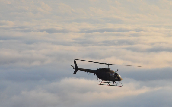 An OH-58 Kiowa helicopter flies above the clouds during the Kiowa's final Florida Army National Guard flight over Florida, Oct. 31, 2014. Photo by 2nd Lt. Justin Phillips