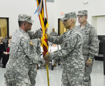 Incoming commander of the 53rd Infantry Brigade Combat Team Col. Ralph Ribas (center) passes the unit guidon to Command Sgt. Maj. Jeffery Young during the change of command ceremony, Jan. 10, 2015, in Pinellas Park, Fla. Photo by Master Sgt. Thomas Kielbasa