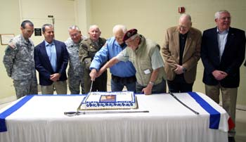 A World War II veteran and German POW cut the commerative cake following a ceremony Jan. 10, 2015, celebrating Camp Blanding Joint Training Center's rich 75-year history. They were joined by previous commanders of the installation. Photo by Sgt. Lindsey Morgan