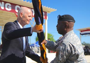 Gov. Rick Scott, Commander in Chief of the Florida National Guard, presents the Florida National Guard flag to Maj. Gen. Michael A. Calhoun, incoming Adjutant General of Florida, during a Change of Command ceremony at the Camp Blanding Joint Training Center (CBJTC), Fla. parade field, Sunday, March 29, 2015. The passing of the colors is a symbolic tradition in which command is relinquished by giving up the flag and then assumed by the incoming commander taking the flag. During this ceremony, Maj. Gen. Emmett R. Titshaw Jr. relinquished command to Calhoun. Photo by Sgt. Spencer Rhodes