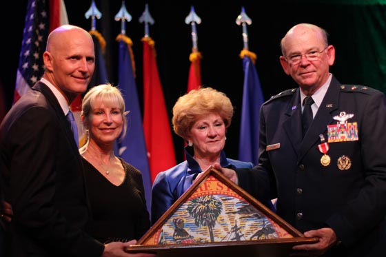 Florida Gov. Rick Scott and Mrs. Ann Scott present a State of Florida flag to Maj. Gen. Emmett Titshaw Jr. and Mrs. Gretchen Titshaw during a retirement ceremony at the World Golf Village in St. Augustine, Fla., March 28, 2015. Photo by Sgt. Spencer Rhodes, 107th MPAD