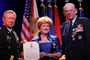 Chief of the National Guard Bureau Gen. Frank Grass (left) and Maj. Gen. Emmett Titshaw Jr. presents an award to Mrs. Gretchen Titshaw (center) during Titshaw's retirement ceremony at the World Golf Village in St. Augustine, Fla., March 28, 2015. Photo by Sgt. Spenser Rhodes, 107th MPAD