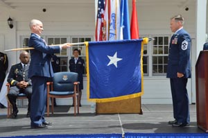 "FLANG Command Chief Master Sgt. Jerry Gardner (right) assists newly promoted Brig. Gen. Thomas Cucchi in unfurling his official ""one star"" flag during a ceremony in St. Augustine, Fla., May 8, 2015. Photo by Master Sgt. Thomas Kielbasa"